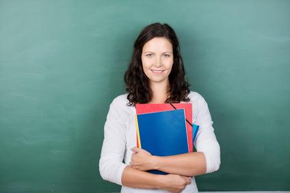 Studentin mit Studienunterlagen steht vor einer Tafel